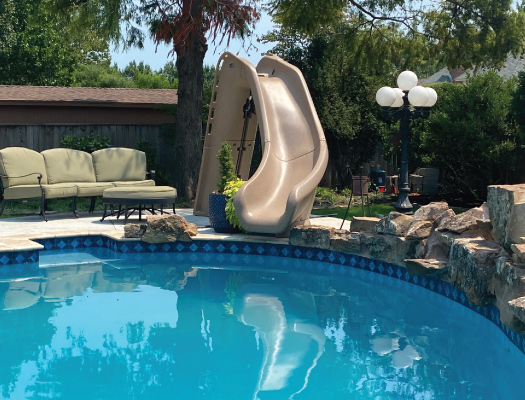waterslide and landscaping by grotto pool designs