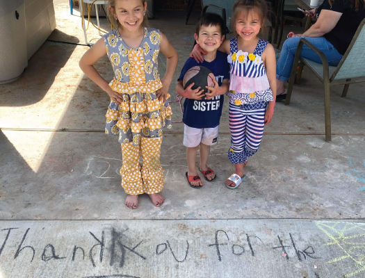 Family with three children with thank you message for pool builders